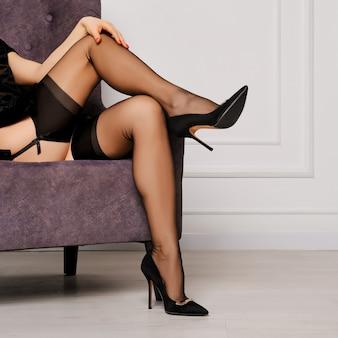 Bijgesneden afbeelding van vrouwelijke benen in kousen en jarretellegordel zittend in een fauteuil