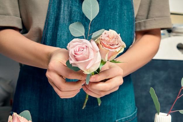Bijgesneden afbeelding van vrouwelijke bloemist op het werk. het schikken van verschillende bloemen in boeket. sluit ter beschikking bloemen. bloemist werkplek. bloemen, decoratie studio. professioneel concept. kopieer ruimte voor ontwerp