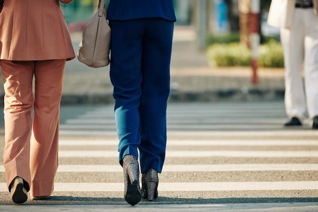 Bijgesneden afbeelding van vrouwelijke ondernemers die de weg oversteken, uitzicht vanaf de achterkant