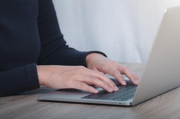 Bijgesneden afbeelding van zakenvrouw die op computer werkt.