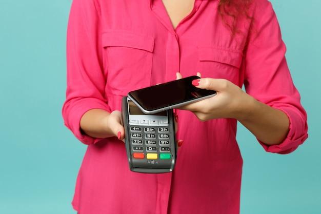 Bijgesneden afbeelding vrouw houdt mobiele telefoon draadloze moderne bankbetaalterminal om creditcardbetalingen geïsoleerd op blauwe turkooizen achtergrond te verwerken. mensen levensstijl concept. bespotten kopie ruimte.