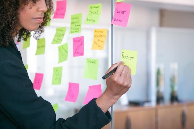 Bijgesneden afro-amerikaanse zakenvrouw schrijven op sticker met marker. hand van de holdingspen van de bureauwerkgever en het maken van nota