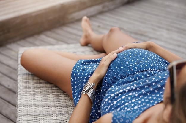 Bijgesneden beeld van jonge blanke vrouw met gebruinde huid genieten van zoete momenten van haar zwangerschap, handen op haar dikke buik te houden.