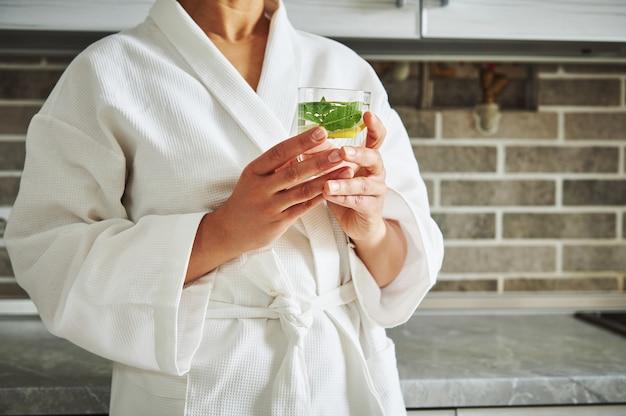 Bijgesneden beeld van onbekende vrouw in witte wafelbadjas met een glas met citroen- en muntwater.
