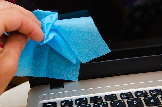 Bijgesneden beeld van vrouw die het scherm van de laptop schoonmaakt met servet in de buurt van notebooks op onscherpe achtergrond op tafel