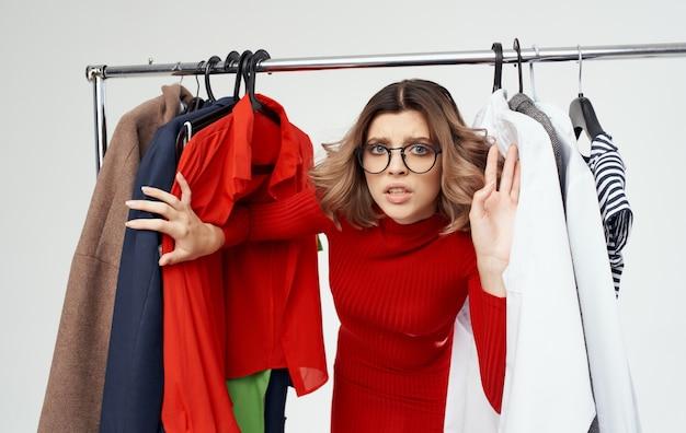 Bijgesneden beeld van vrouw in de buurt van modieuze kleding in de kleedkamer.