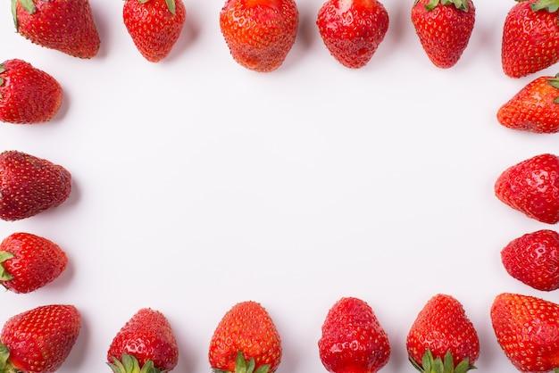 Bijgesneden bovenkant boven bovenaanzicht foto van aardbeien opgesteld aan de zijkanten waardoor het midden leeg is op een witte achtergrond