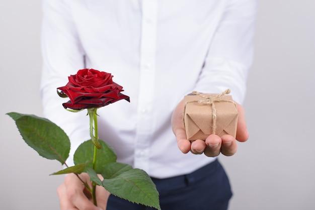 Bijgesneden close-up foto portret van knappe charmante gelukkig vrolijke positieve man met klein cadeautje en heldere roos geïsoleerde grijze achtergrond
