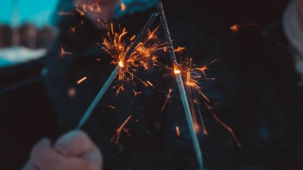 Bijgesneden close-up foto van bengaalse vuurstokken, sprankelend, brandend, minnaarshanden die vuurstokken bij elkaar houden, vergadering, team, groeten, gefeliciteerd, vrolijk kerstfeest