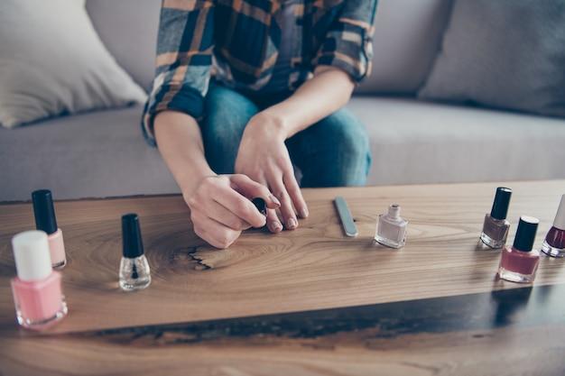 Bijgesneden close-up foto van dame gemaakt correctie vinger nagels poolse afwerking vacht bedrijf hand op tafel dragen casual kleding zitten gezellige bank appartement binnenshuis toe te passen