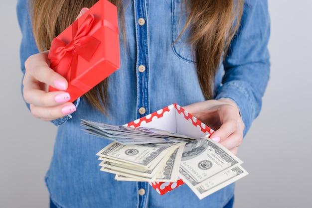 Bijgesneden close-up foto van gelukkige gelukkige verbaasde verbaasd koele dag dame stapel stapel geld vinden in kleine doos met strik geïsoleerd grijze achtergrond