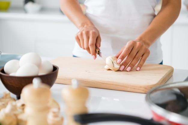 Bijgesneden close-up foto van stijlvolle vrouw gastronomische groente gesneden paddestoel op snijplank bereiden fest hebben kom met verse eieren in witte huiskeuken