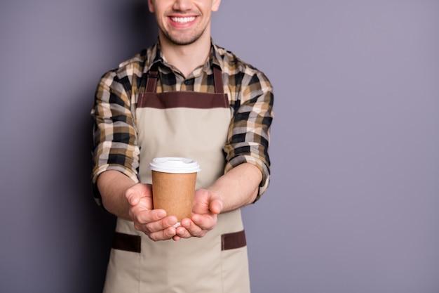 Bijgesneden close-up foto van vrolijke positieve knappe ober serveert u koffiekopje zoals besteld geïsoleerde grijze kleur muur