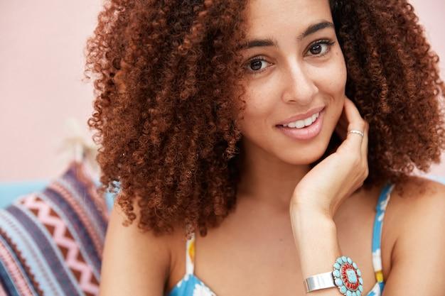 Bijgesneden close-up shot van aangenaam ogende tevreden jonge vrouw met donkere ogen, gezonde huid en zachte glimlach