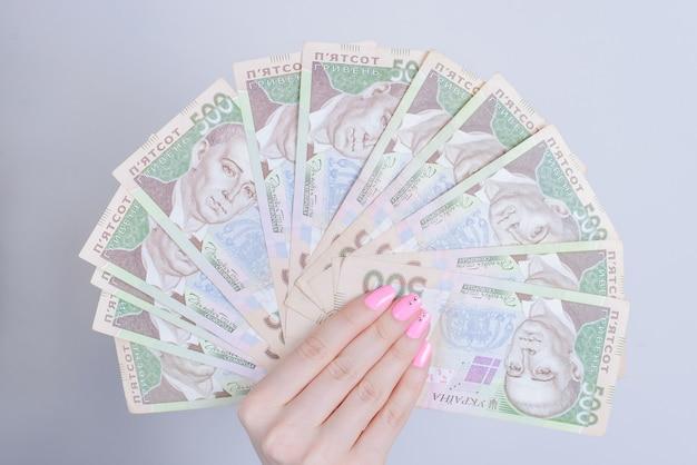 Bijgesneden close-up van de handen van de dame met pak og oekraïens geld tonen rijkdom geïsoleerde grijze muur