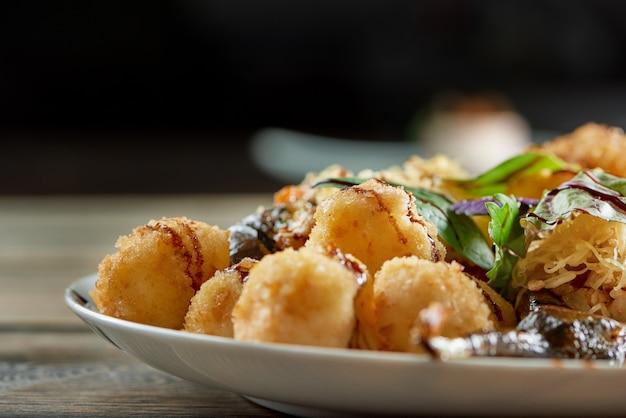 Bijgesneden close-up van een bord vol met gebakken kaas ballen op de houten tafel op donkere muur copyspace schotel maaltijd heerlijke smakelijke voeding vet calorieën ongezond.