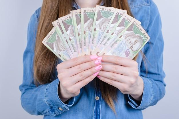 Bijgesneden close-up van oekraïne geld in handen houden mooie dame geïsoleerde grijze muur