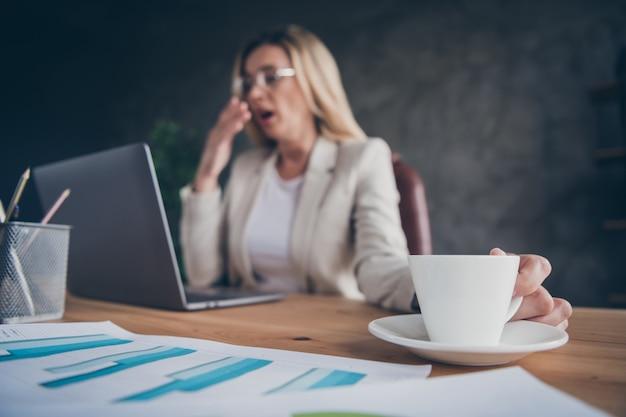 Bijgesneden close-up vermoeide gapende zakelijke dame met kopje koffie om wakker te worden en te beginnen met werken in de ochtend