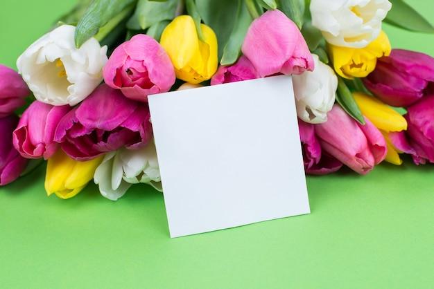 Bijgesneden close-upfoto van kleine papieren kaart met lege lege plek voor tekst en groot boeket op groene tafel