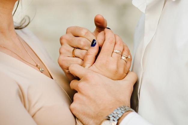 Bijgesneden foto jong getrouwd stel houdt handen met ringen, man en vrouw buitenshuis. achter mening van paar dat zich op aard bevindt