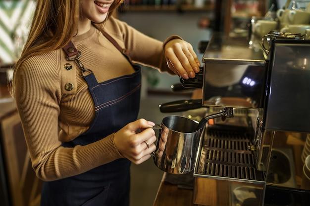 Bijgesneden foto, jong meisje, barista stomende melk in de moderne coffeeshop