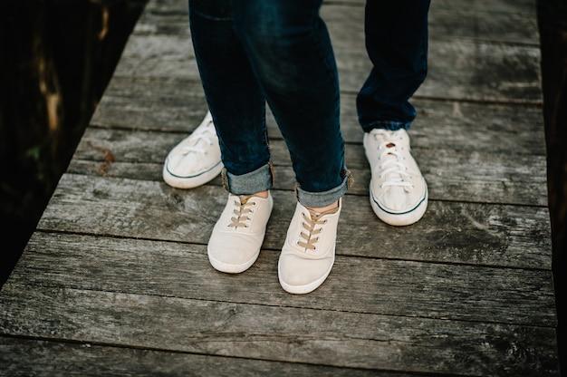 Bijgesneden foto jonge benen in sneakers, echtpaar, man en vrouw op een houten brug in de buurt van meer. achter mening van paar dat zich op pijler bevindt. onderste helft.