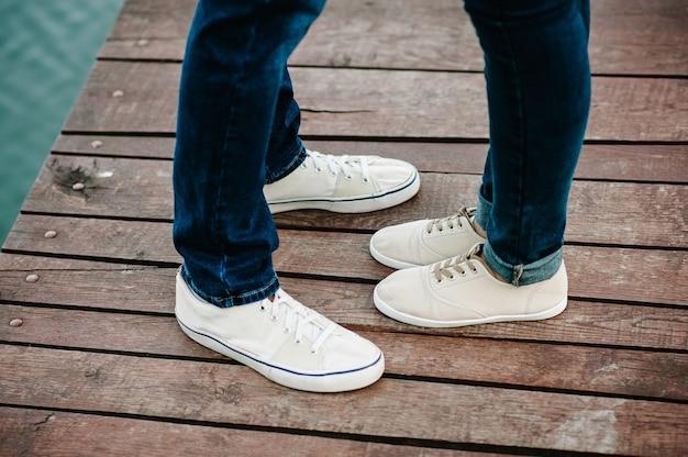 Bijgesneden foto jonge benen in sneakers, echtpaar, man en vrouw op een houten brug in de buurt van meer. achter mening van paar dat zich op pijler bevindt.