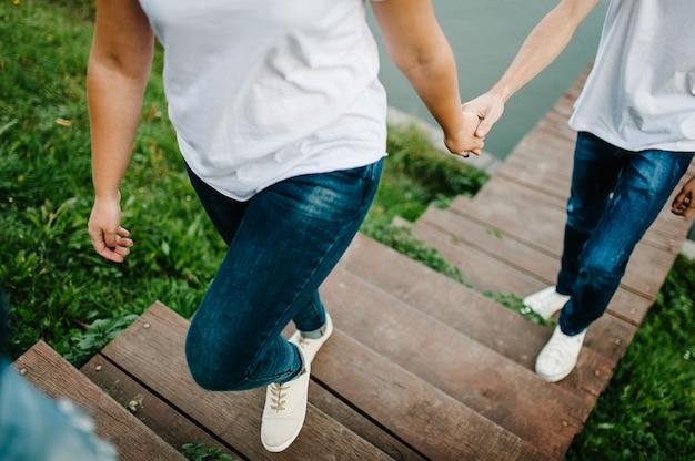 Bijgesneden foto jonge geliefden getrouwd stel, man en vrouw, hand in hand gaan de trap beklimmen op een houten brug in de buurt van het meer. vooraanzicht van paar op pier.