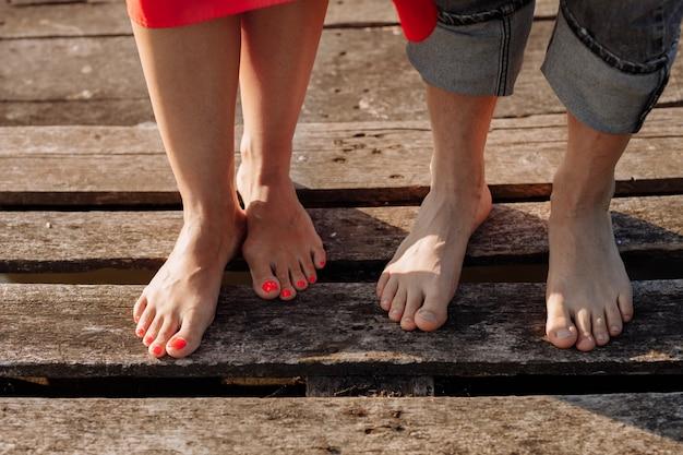 Bijgesneden foto jonge geliefden getrouwd stel, man en vrouw, hand in hand op een houten brug in de buurt van meer. achterk bezichtiging, van, paar, staand, op, pier. onderste helft. plaats voor tekst en ontwerp. detailopname.