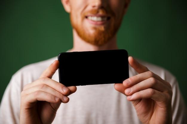 Bijgesneden foto roodharige bebaarde man in witte t-shirt maakt een foto op smartphone mobiel