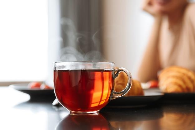 Bijgesneden foto van blanke vrouw zittend aan tafel in flat, met hete thee in glas