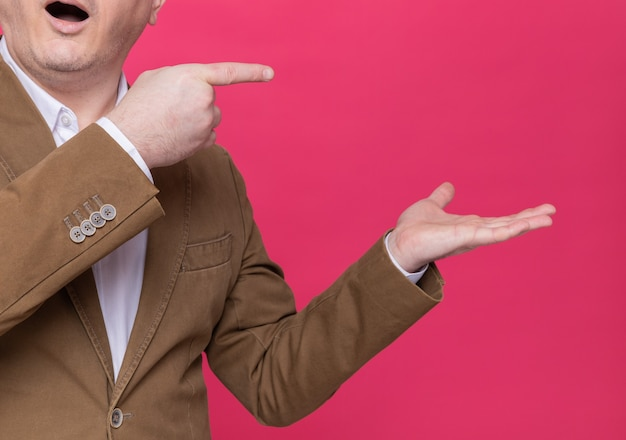 Bijgesneden foto van blij en verrast man van middelbare leeftijd in pak wijzend met wijsvingers naar de zijkant