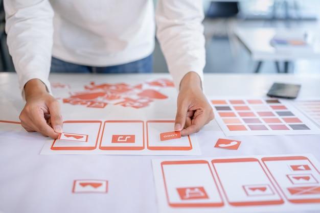 Bijgesneden foto van creatief ux ui-ontwerpteamontwerp. ontwikkeling van mobiele applicatie van prototypes en draadmodel lay-out.