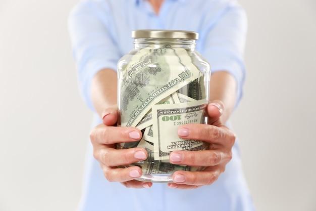 Bijgesneden foto van de handen van de vrouw met glazen pot met dollarbiljetten