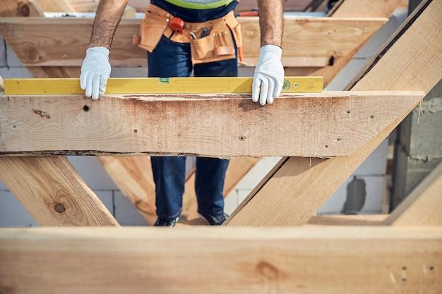 Bijgesneden foto van een bekwame bouwer die een waterpasinstrument gebruikt op een bouwplaats