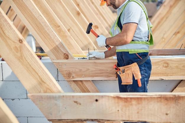 Bijgesneden foto van een gefocuste bouwer die een hamer en een spijker vasthoudt op een bouwplaats
