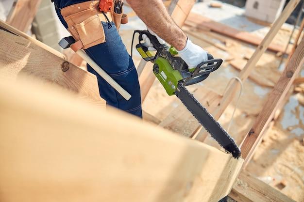 Bijgesneden foto van een geschoolde arbeider die een kettingzaagsnijmachine gebruikt op stukken bouwhout