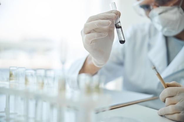 Bijgesneden foto van een jonge blanke mannelijke wetenschapper die een biologische substantie in zijn hand analyseert
