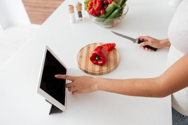 Bijgesneden foto van een jonge vrouw die het recept leest van de tabletcomputer.