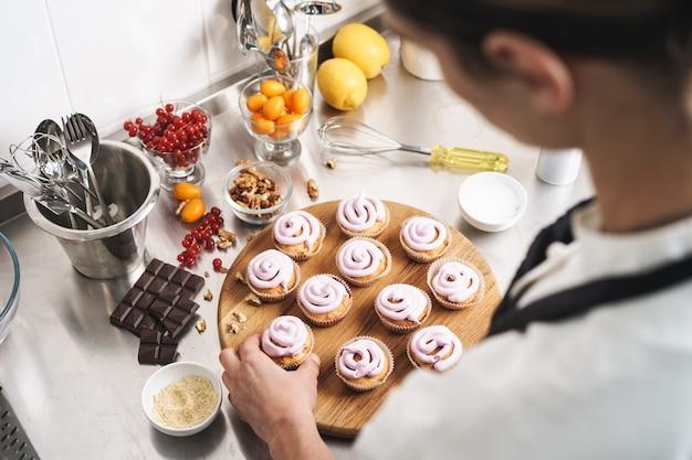 Bijgesneden foto van een knappe jonge kokchef-kok in de keuken die snoepjes binnenshuis kookt.