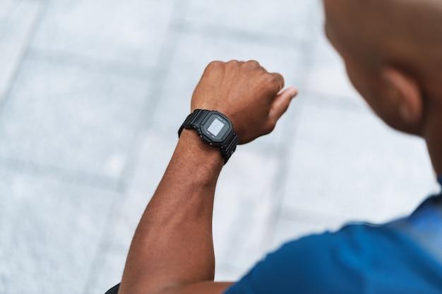 Bijgesneden foto van een knappe sterke afrikaanse sportman die buiten naar het horloge kijkt.