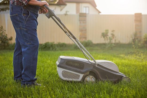 Bijgesneden foto van een man die zijwaarts staat met een grasmaaier op een groen gazon