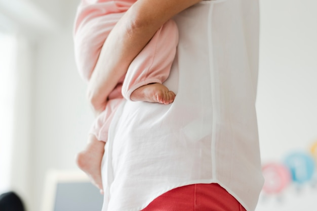 Bijgesneden foto van een ouder die een baby draagt