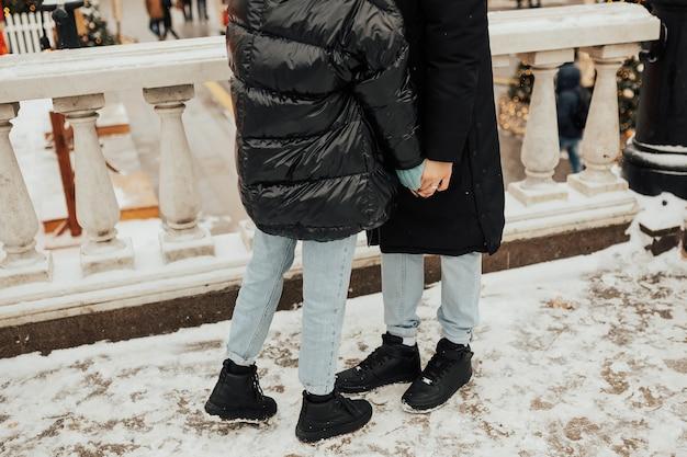 Bijgesneden foto van een paar hand in hand en staande op de besneeuwde straat