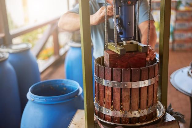 Bijgesneden foto van een persoon die sap uit druiven haalt met behulp van een wijnpers