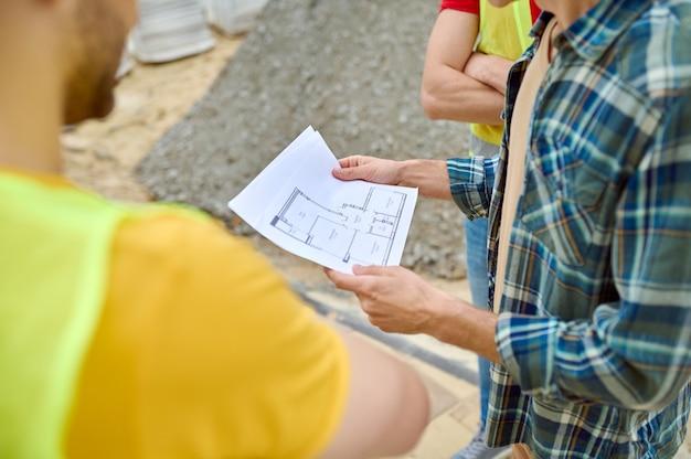 Bijgesneden foto van een professionele architect met huisplannen in zijn handen die naast twee bouwers in veiligheidsvesten staat