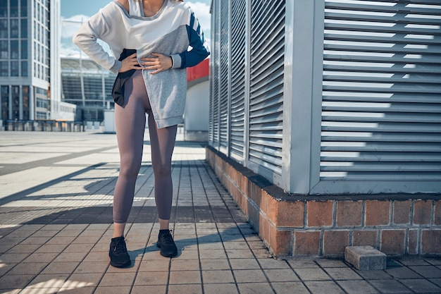 Bijgesneden foto van een slanke jonge vrouw met haar handen op haar buik die buiten staat