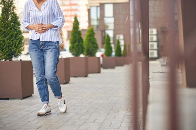Bijgesneden foto van een slanke vrouw die over straat loopt met haar handen op de buik