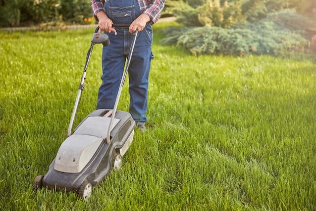Bijgesneden foto van een tuinman die een maaier duwt terwijl hij een gazon maait
