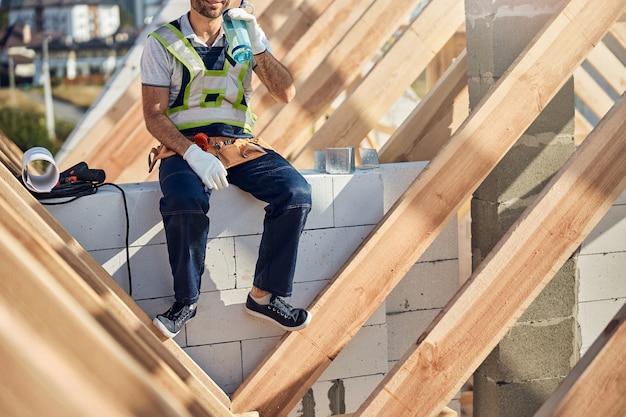 Bijgesneden foto van een vermoeide bouwer die op een bouwplaats zit en uit zijn waterfles drinkt